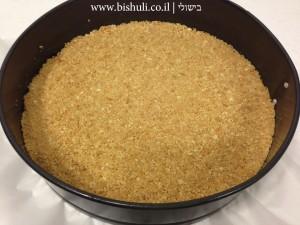 עוגת גבינה ושמנת חמוצה - פירורי ביסקוויטים עם חמאה בתבנית